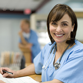 physician smiling and looking at camera with paperwork in hand
