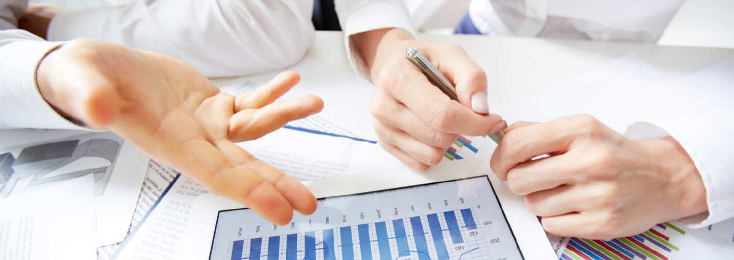 Employees reviewing reports on a tablet